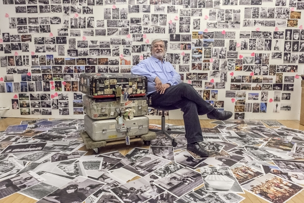 June 25, 2013. Manhattan, New York. Jean-Pierre Laffont in front of 'Photographer's Paradise' book wall. He sits next to his suitcases that moved around the world with him. Photograph by Sam Matamoros.
